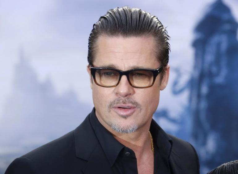 447496-actor-brad-pitt-arrives-for-a-maleficent-costume-display-at-kensington
